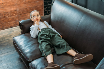 adorable little child in stylish clothing relaxing on couch at home