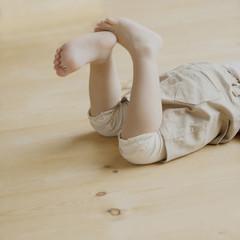 床に寝そべる女の子の足元