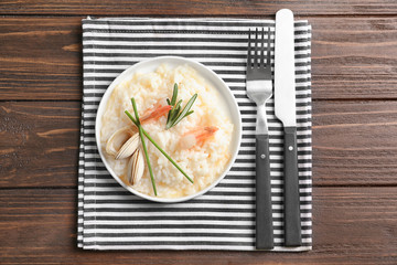 Plate with delicious seafood risotto on wooden table
