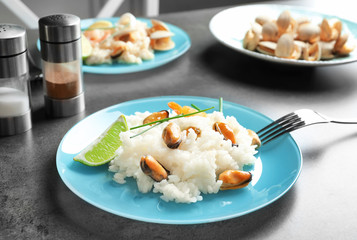 Plate with delicious seafood risotto on table