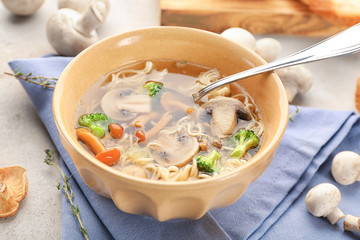 Bowl with mushroom soup on table