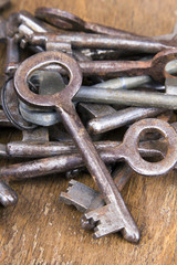 Old rusty keys on wooden background