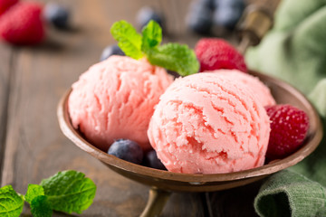 Raspberry ice cream scoops in copper bowl with forest berries and mint decoration. Summer food concept. Macro shoot.