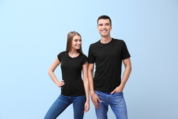 Young woman and man in black t-shirts on color background. Mockup for design