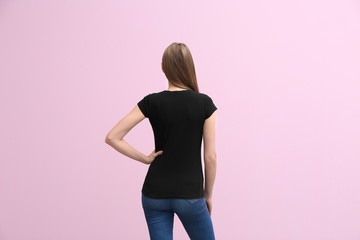 Young woman in black t-shirt on color background. Mockup for design