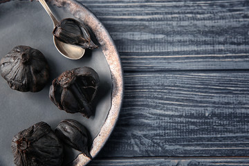 Plate with black garlic (Allium sativum) on wooden table