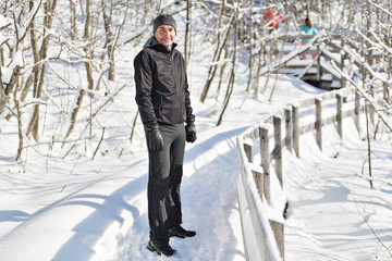 man jogging on snow in forest, bautiful sunny winter day