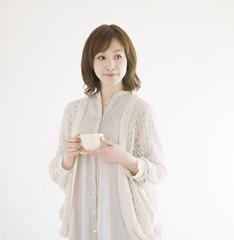 コーヒーカップを持ち微笑む女性
