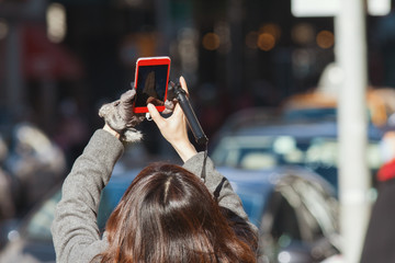Woman on street take pictures of new york Skyscraper on smartphone