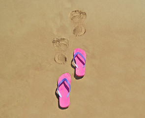 summer flip flops on the beach with footsteps on sand - summer vacation icon