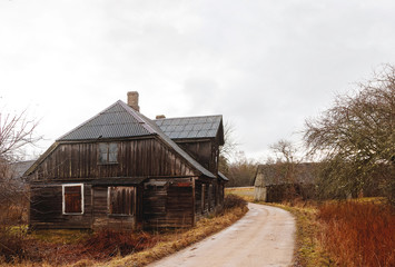 standing at the edge of the road, an old wooden house