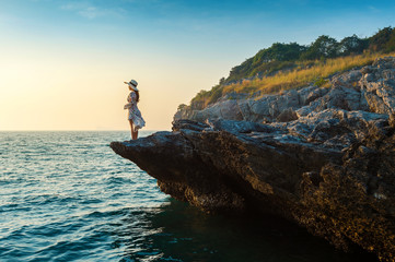 Wall Mural - Young woman standing on the top of rock and looking at the seashore and sunset in Si chang island.