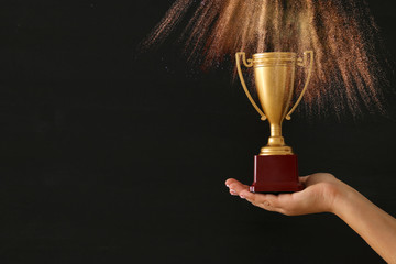 low key image of a woman holding a trophy cup over dark background.