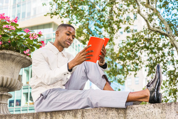 Young African American Man reading book outside. Young black man wearing light color jacket, gray pants, leather shoes, sitting on top of half wall by street in Manhattan, New York, reading red book..