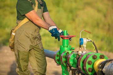 Oil worker is turning valve on the oil pipeline.