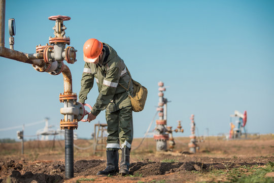 Oil worker is turning valve on the oil pipeline, oil deposit on the background.