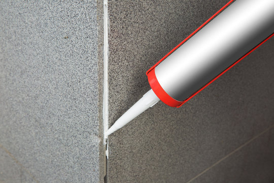 Sealant gun crackcovers the crack in the floor of the wall tile concrete