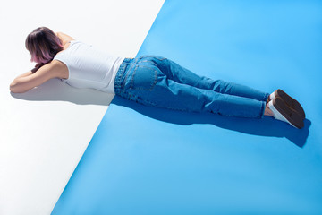 stylish girl lying on white and blue floor in jeans