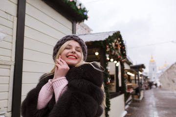 Street portrait of joyful young woman wearing stylish knitted hat and fur coat, posing at the Christmas fair. Empty space