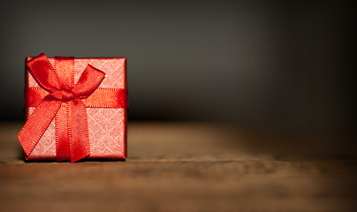 Valentines concept red gift box on wooden table. Blurred background.