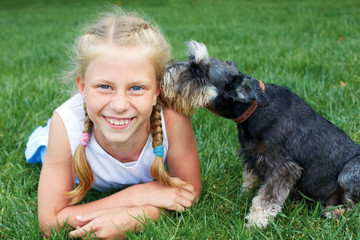 Happy child lying on the grass with her dog in the park. The Secret of Friends
