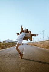Cheerful young woman having fun on road