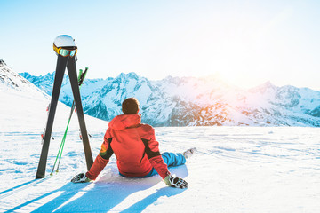 Skier athlete sitting in alpes mountains on sunny day Wall mural