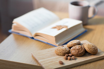 Fototapete - oat cookies, almonds and book on table at home