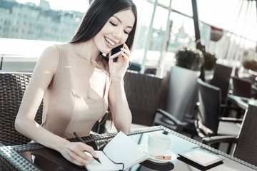 Glade to hear you. Joyful pleasant stylish girl sitting by the table having phone conversation and smiling.