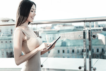 Gadgets in life. Smart cute clever lady standing near the edge of rooftop using the tablet and looking at the screen.