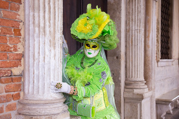 Venice Carnival - Female Venetian Mask in green elegant costume on St. Mark's Square in Venice
