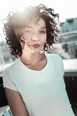Young and romantic. Thoughtful cute curly girl tilting head looking straight and feeling good herself.