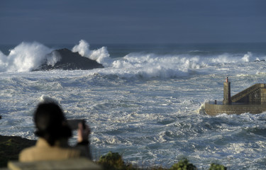 A woman takes pictures of waves as they crash against a lighthouse in the port town of Tapia de Casariego