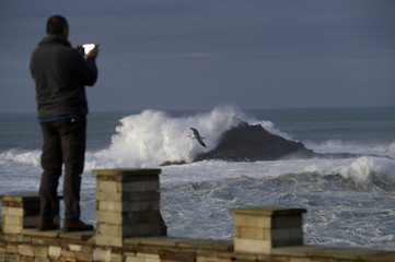 A man takes pictures of waves as they crash against a lighthouse in the port town of Tapia de Casariego