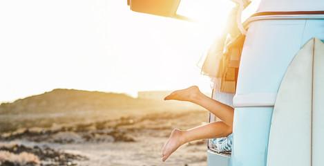Legs view of happy surfer girl inside minivan at sunset