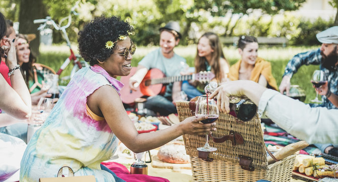 Group of friends making picnic lunch and drinking wine outdoor