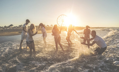 Happy friends having fun inside the ocean at sunset - Young playing with water and laughing together outdoor in summer vacation - Friendship, youth lifestyle, holidays and travel concept