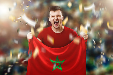 A Moroccan fan, a fan of a man holding a Morocco national flag in his hands. Soccer fan in the stadium. Mixed media