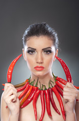 Portrait of beautiful young woman with red hot chili peppers, fashion model with creative food vegetable make up looking sideways into empty space, isolated against black background.Red chili paprika.