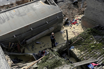 Man takes pictures of the damaged left by the car of a cargo train that ran off the tracks knocking a home in the municipality of Ecatepec