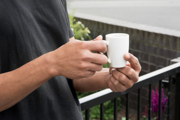 Close up of young man's hands holding a cup of coffee in an outdoor cafe. Selective focus
