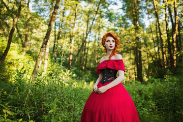 Beautiful red-haired girl in a red dress and in black corset on a green background. A woman with red hair in a summer forest