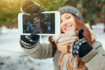 Young woman takes selfie in winter forest
