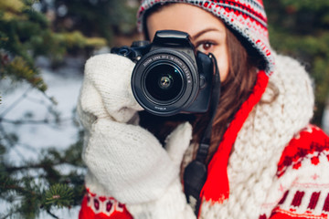 Young photographer takes pictures of winter forest
