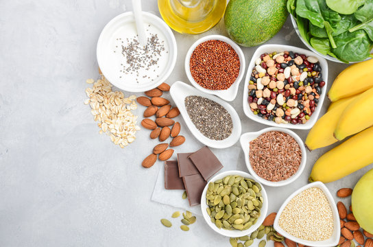 Healthy food nutrition dieting concept. Banana, chocolate, spinach, avocado, apple, quinoa, chia, flax seeds, yogurt, almond, beans, oat, pumpkin seeds, olive oil. Top view, flat lay, copy space.