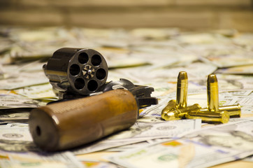 The blurred weapon with bullets laid down on blurred dollars
