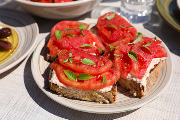 Sandwiches with feta cheese, fresh tomatoes, basil leaves as an appertizer.