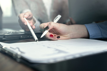 Two businesswoman discuss about grafic with pen in the hands