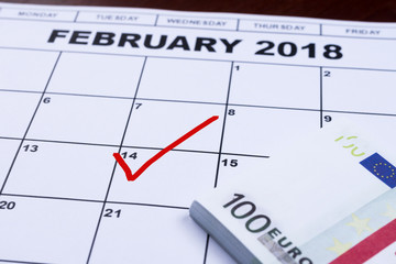 February 14 marked on the calendar and the money set aside for gifts.