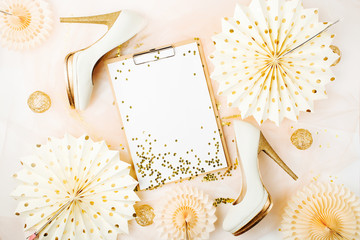 Clipboard and Female shoes with golden decorations. Flat lay, top view trendy holiday concept.